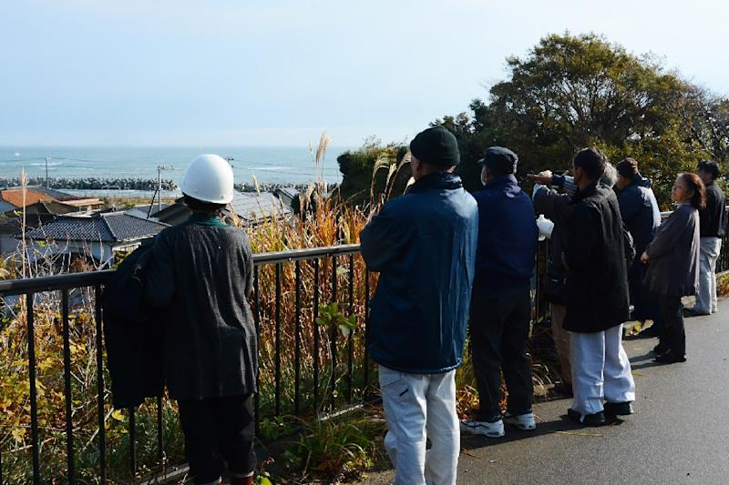 Local residents look out to sea from higher ground after evacuating their homes following a 6.9 magnitude earthquake and tsunami alert in Iwaki, Fukushima prefecture, on November 22, 2016 (AFP Photo/JIJI PRESS)