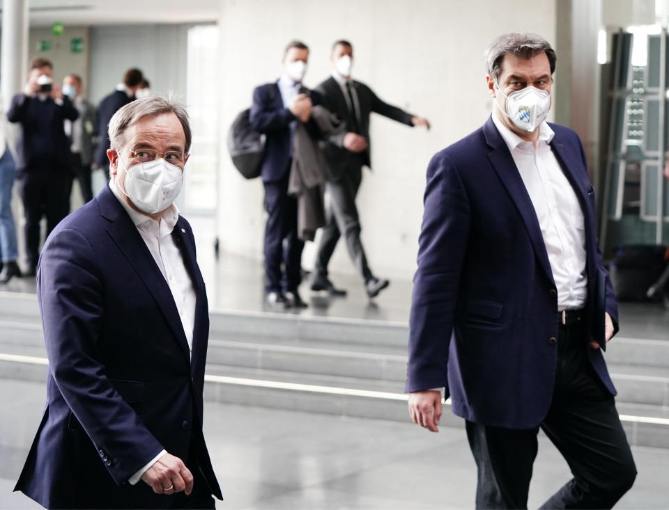 The chairman of the German Christian Democratic Party (CDU), ArminLaschet, left, and the chairman of the German Christian Social Union (CSU), Markus Soeder, right, arrive for a statement folowing a closed meeting of the federal palrliament factions of both partys in Berlin, Germany, Sunday, April 11, 2021. The two party chairmen and German state governors want to become the center-right candidate for the country's Sept. 26 national election, the German news agency dpa reported Sunday. (Michael Kappeler/dpa via AP)