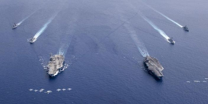 Aircraft in formation over the USS Nimitz and USS Ronald Reagan.