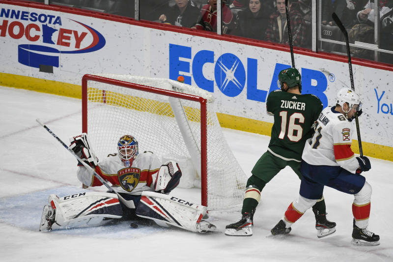 Florida Panthers goalie Sergei Bobrovsky, left, stops a shot by Minnesota Wild winger Jason Zucker (16) as Panthers defenseman Riley Stillman pushes Zucker past the goalduring the first period of an NHL hockey game Monday, Jan. 20, 2020, in St. Paul, Minn. (AP Photo/Craig Lassig)