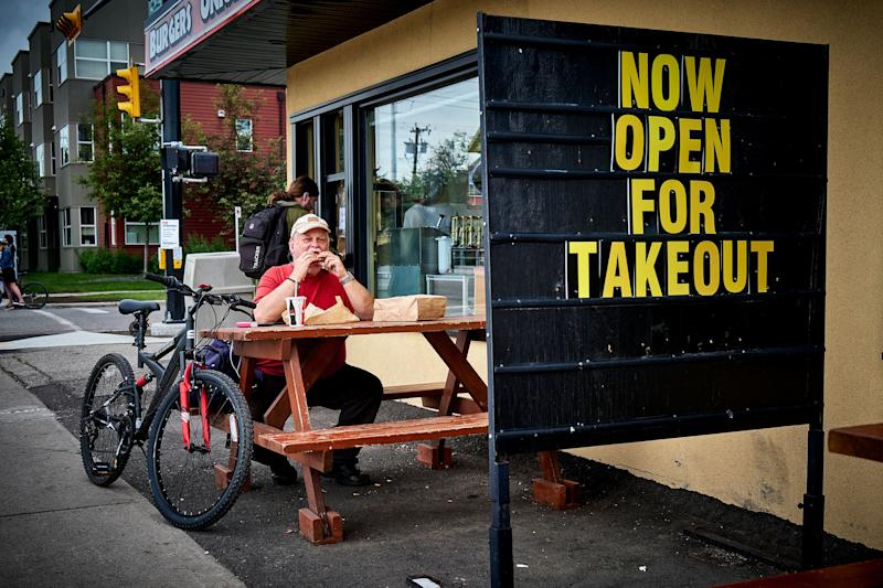 A patron enjoys takeout in Calgary, Alta., on June 23, 2020, amid a worldwide COVID-19 pandemic. (Photo: CP/Jeff McIntosh)