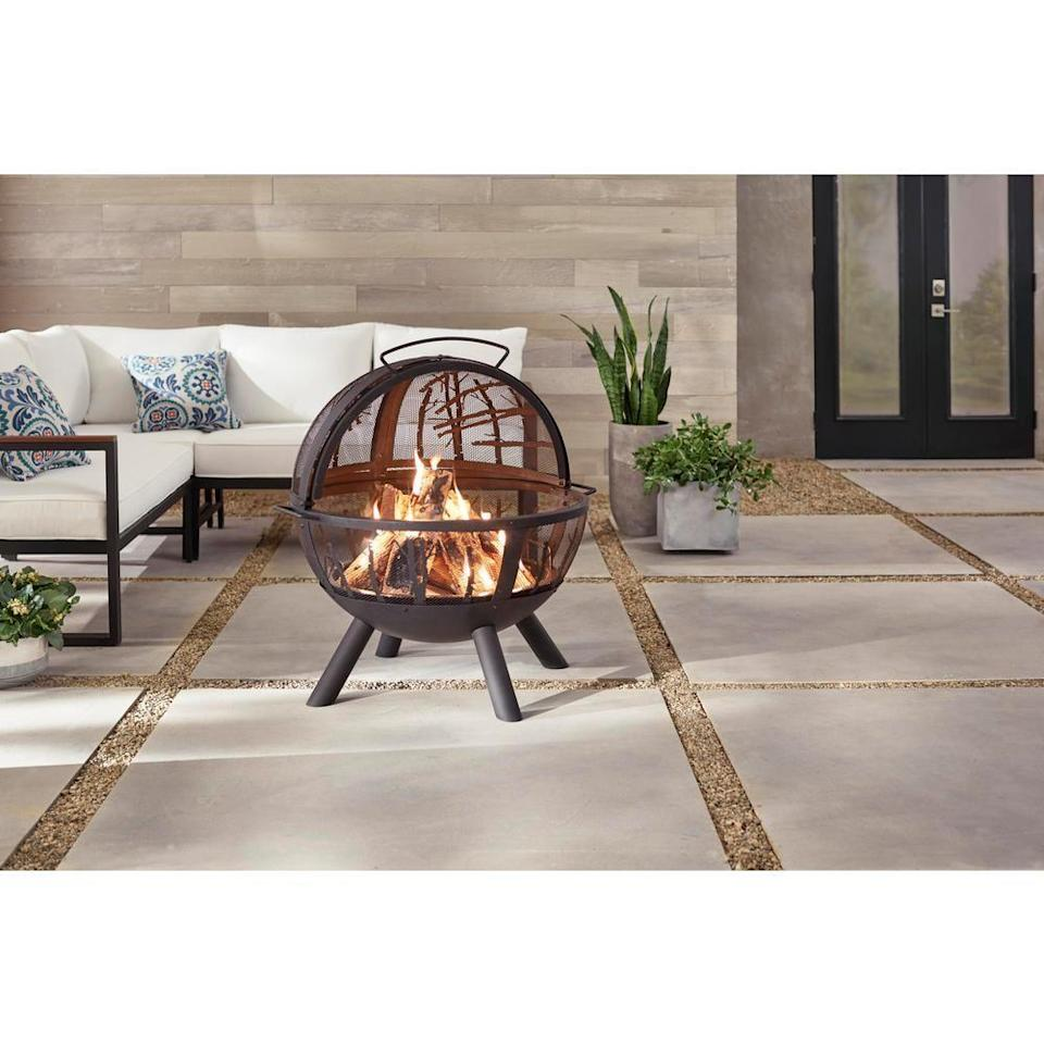 """<p><strong>Hampton Bay</strong></p><p>homedepot.com</p><p><strong>$149.00</strong></p><p><a href=""""https://go.redirectingat.com?id=74968X1596630&url=https%3A%2F%2Fwww.homedepot.com%2Fp%2FHampton-Bay-Briarglen-Fire-Ball-with-Tree-Branches-118023%2F309397794&sref=https%3A%2F%2Fwww.countryliving.com%2Fdiy-crafts%2Fg31966151%2Foutdoor-fireplace-ideas%2F"""" rel=""""nofollow noopener"""" target=""""_blank"""" data-ylk=""""slk:Shop Now"""" class=""""link rapid-noclick-resp"""">Shop Now</a></p><p>You've never seen a fire pit quite like this sphere-shaped design. Tree branch details on the screen add an unexpected touch.</p>"""