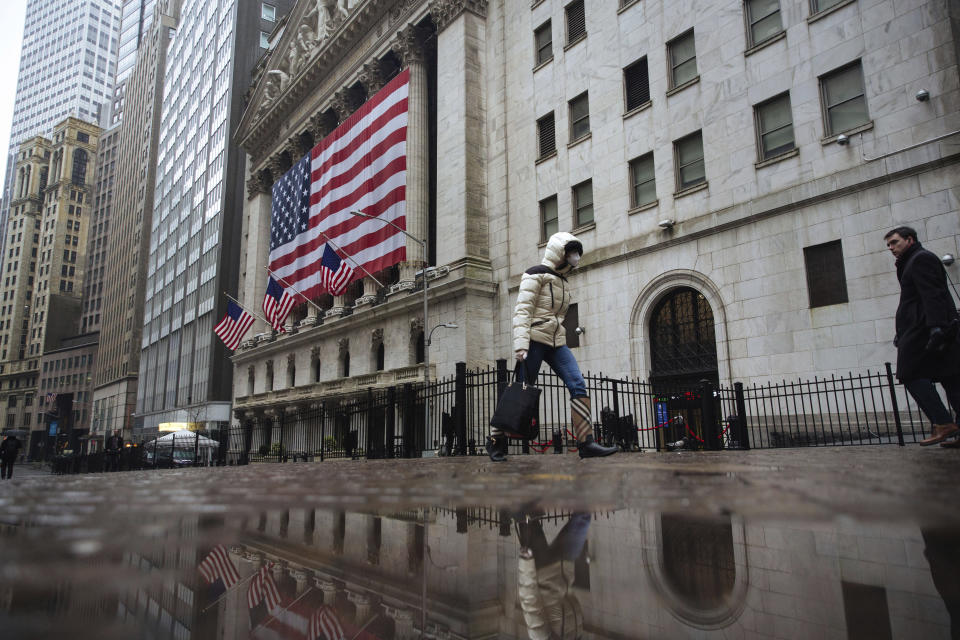 FILE - In this Thursday, March 19, 2020 file photo, a pedestrian wearing a face mask and gloves walks past the New York Stock Exchange in New York. On March 23, 2020, the S&P 500 fell 2.9%. In all, the index dropped nearly 34% in about a month, wiping out three years' worth of gains for the market. (AP Photo/Kevin Hagen)