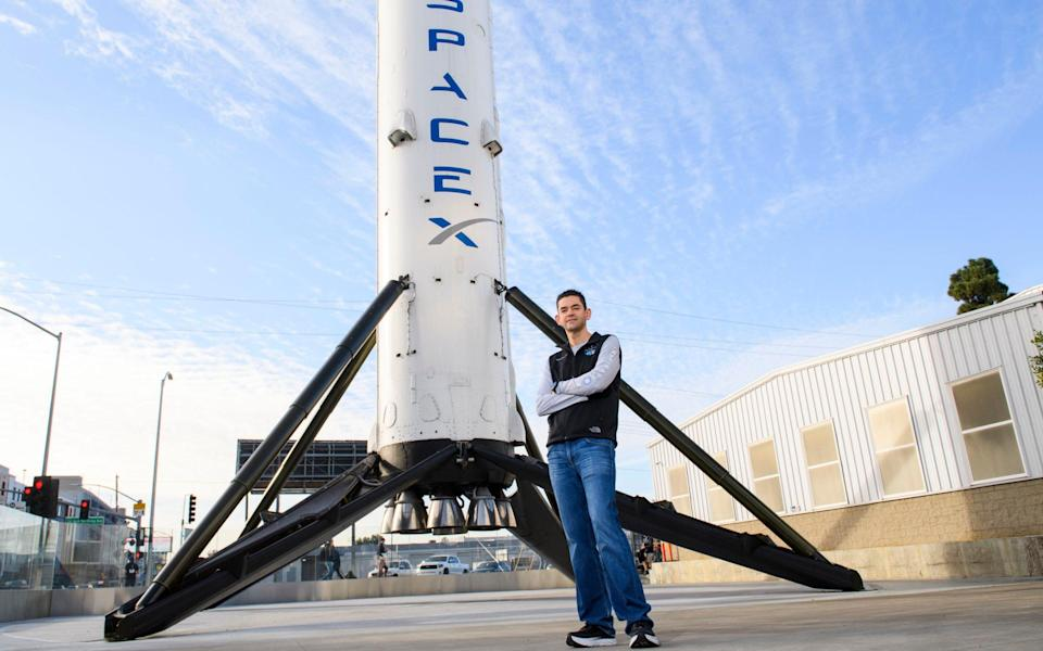 Inspiration4 mission commander Jared Isaacman, founder and chief executive officer of Shift4 Payments, stands for a portrait in front of the recovered first stage of a Falcon 9 rocket  - PATRICK T. FALLON /AFP