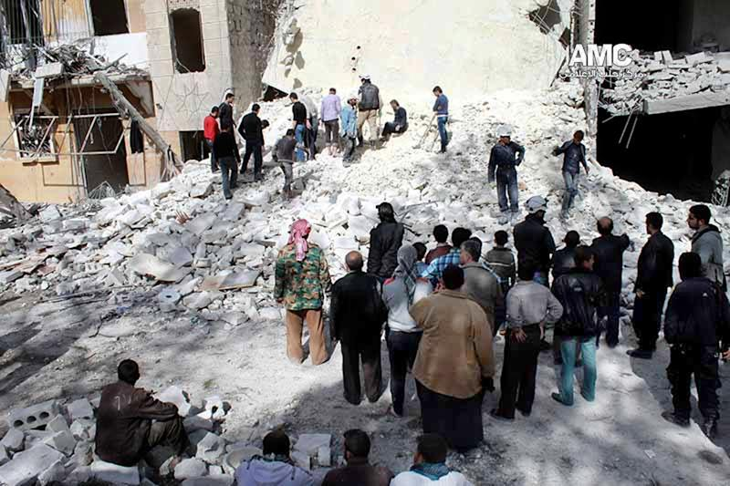 In this picture taken on Wednesday, March 5, 2014, provided by the anti-government activist group Aleppo Media Center (AMC), which has been authenticated based on its contents and other AP reporting, Syrians inspect the rubble of destroyed buildings following a Syrian government airstrike in Aleppo, Syria. (AP Photo/Aleppo Media Center AMC)