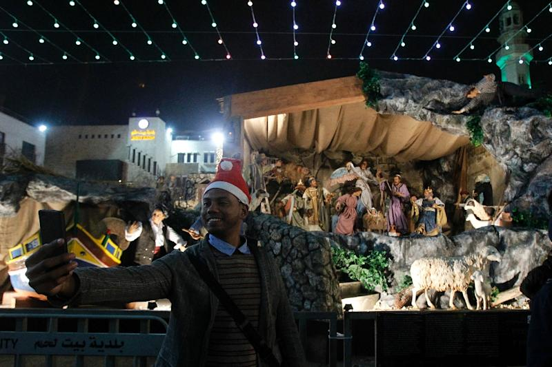 A man takes a selfie at the Manger Square outside the Church of the Nativity during Christmas Eve celebrations Bethlehem (AFP Photo/Musa AL SHAER)
