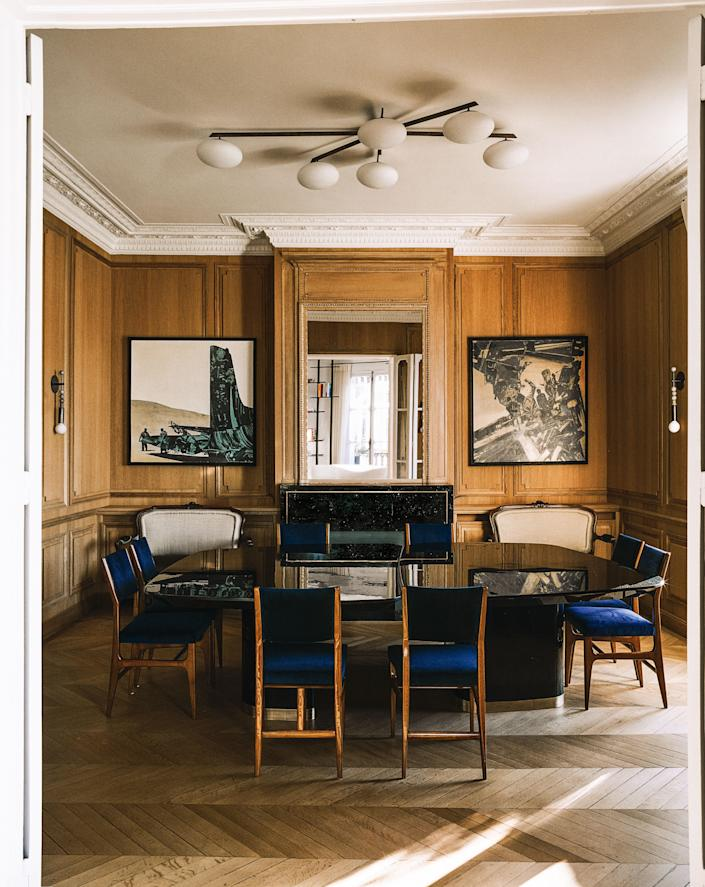 Gio Ponti chairs surround a Stanislas-designed dining table. Angelo Lelli ceiling light; paintings by Gianni Bertini.