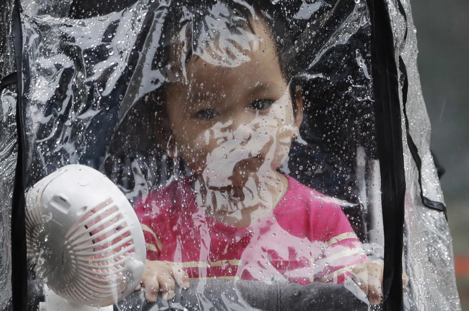 A baby looks out through the raindrop canopy in a rain caused by Typhoon Chanthu in Taipei, Taiwan, Sunday, Sept. 12, 2021. Typhoon Chanthu drenched Taiwan with heavy rain Sunday as the storm's center passed the island's east coast heading for Shanghai. (AP Photo/Chiang Ying-ying)