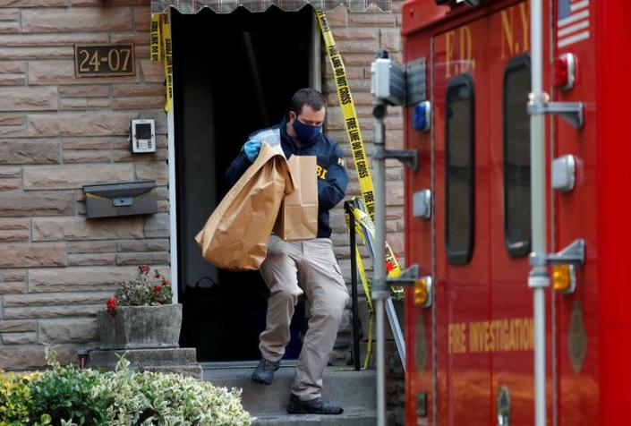 FBI officer removes evidence bags from a house where police say bomb-making materials were found, in New York