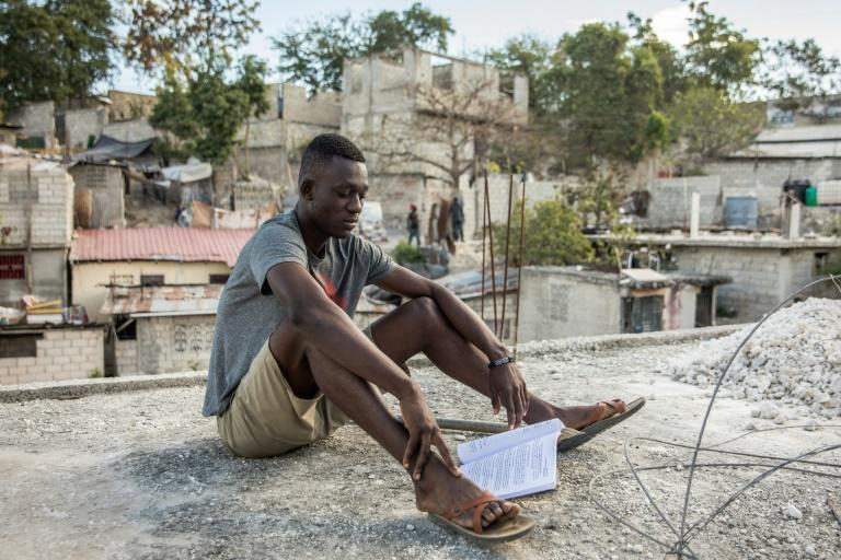 Kervens Casseus, 20, studies on the roof of his uncle's house in Port-au-Prince on February 18, 2021, one of many young Haitians deeply affected by political crisis, economic inequality and street crime