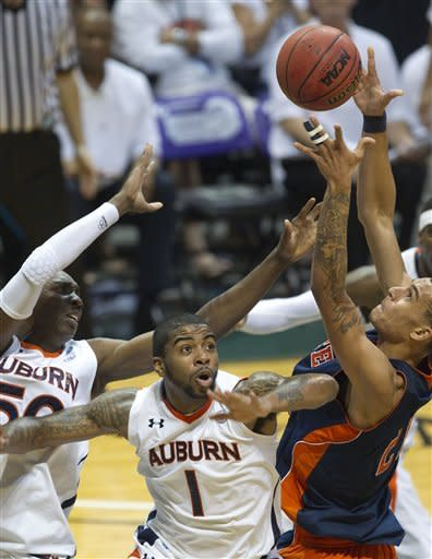 Auburn center Willy Kouassi (50) and Varez Ward (1) battle UTEP center John Bohannon (21) for a rebound in the first half of an NCAA college basketball game on Sunday, Dec. 25, 2011, in Honolulu. (AP Photo/Eugene Tanner)