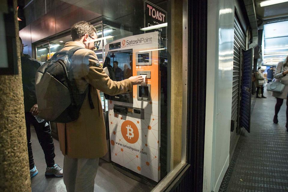 A customer uses a Bitcoin machine in Old Street underground station in London (PA) (PA)