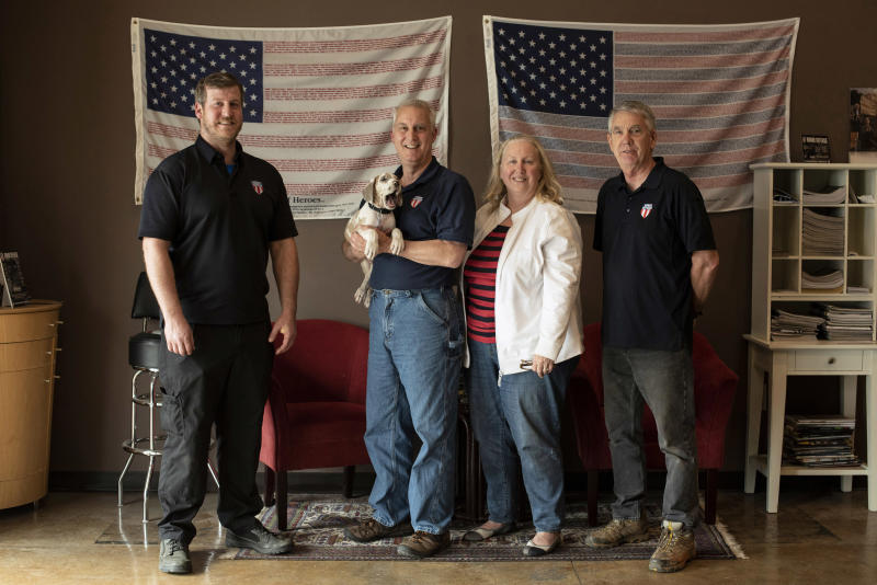 FILE - In this April 25, 2018, file photo, the owners and employees of Honor Defense, a gunmaker in Gainesville, Ga., pose in the company's lobby. Standing, left to right, are Pete Ramey, who works on the assembly line, Gary Ramey, the company's owner, his wife and company business manager, Pam Ramey, and Richard Moore, who works on the assembly line. Gary Ramey says that this year's SHOT Show, officially starting Tuesday, Jan. 21, 2020, will be especially critical to see products and meet suppliers for the parts he uses to make his line of handguns. (AP Photo/Lisa Marie Pane, File)