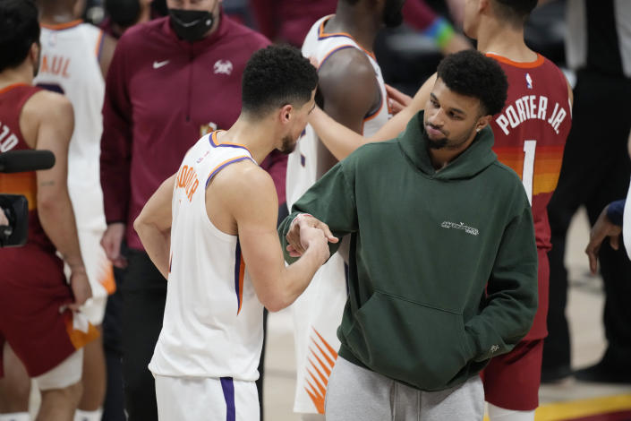 Phoenix Suns guard Devin Booker, left, shakes hands with injured Denver Nuggets guard Jamal Murray after the second half of Game 4 of an NBA second-round playoff series, Sunday, June 13, 2021, in Denver. Phoenix won 125-118 to sweep the series. (AP Photo/David Zalubowski)