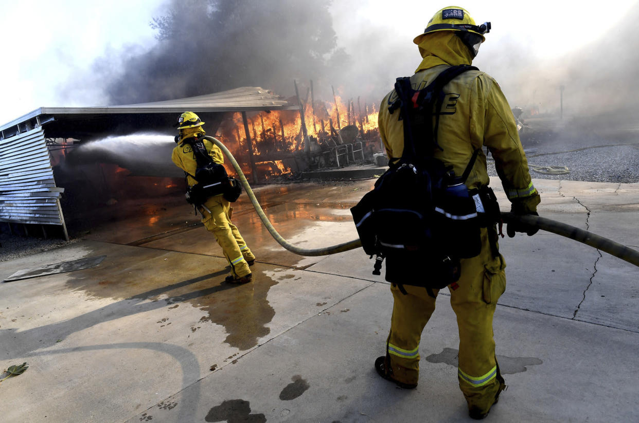 Firefighters try to protect surrounding homes as they battle the Sandalwood Fire in the Villa Calimesa Mobile Home Park in Calimesa, Calif., on Thursday, Oct. 10, 2019. Burning trash dumped along a road sparked a wildfire Thursday that high winds quickly pushed across a field of dry grass and into a Southern California mobile home park, destroying dozens of residences. (Photo: Jennifer Cappuccio Maher/The Orange County Register/SCNG via AP)