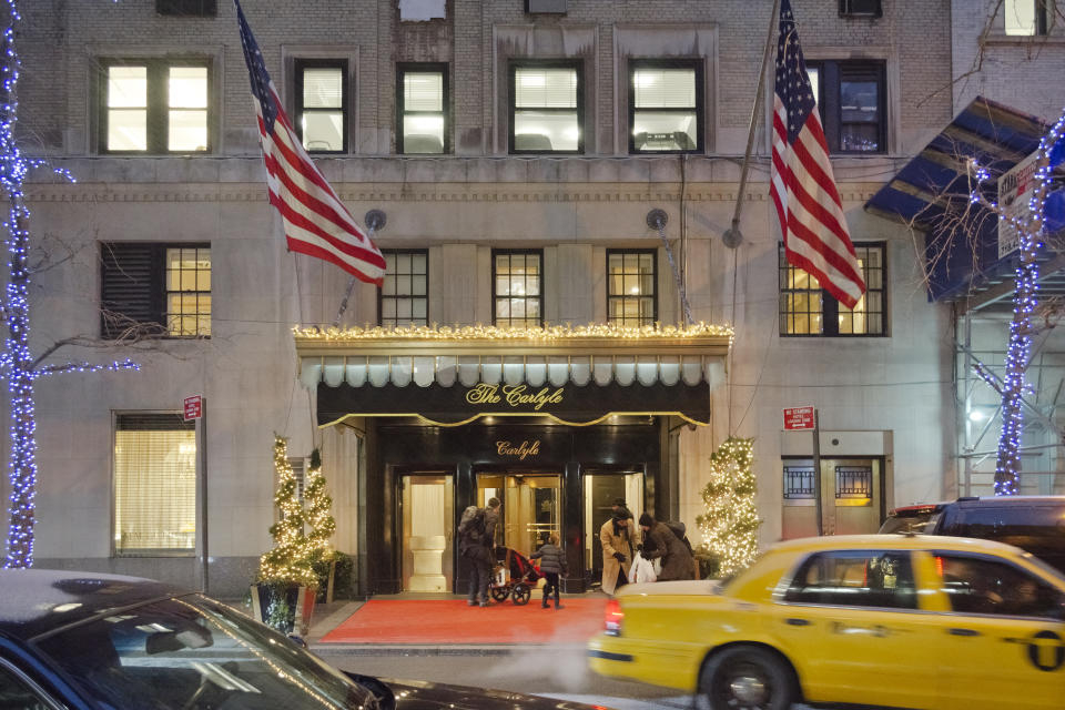 New York, USA - January 25, 2013: The Carlyle is a  luxury hotel located at 35 East 76th Street on Madison Avenue, it is both rental rooms and suites hotel and privately owned residence. People in front of the entrance, the doorman is helping a guest, cars are passing on the street and it is snowing.