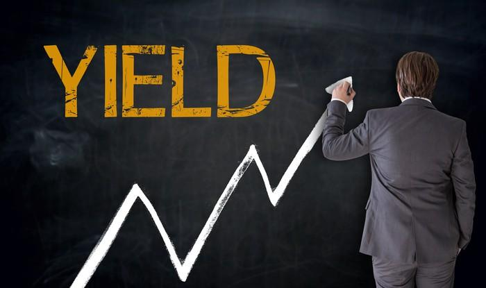 Businessman drawing a line going up on a chalkboard beneath the word yield.