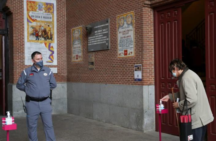 A woman uses a hand sanitiser as she enters the Las Ventas bullring ahead of the first bullfight since the start of the COVID-19 pandemic, in Madrid