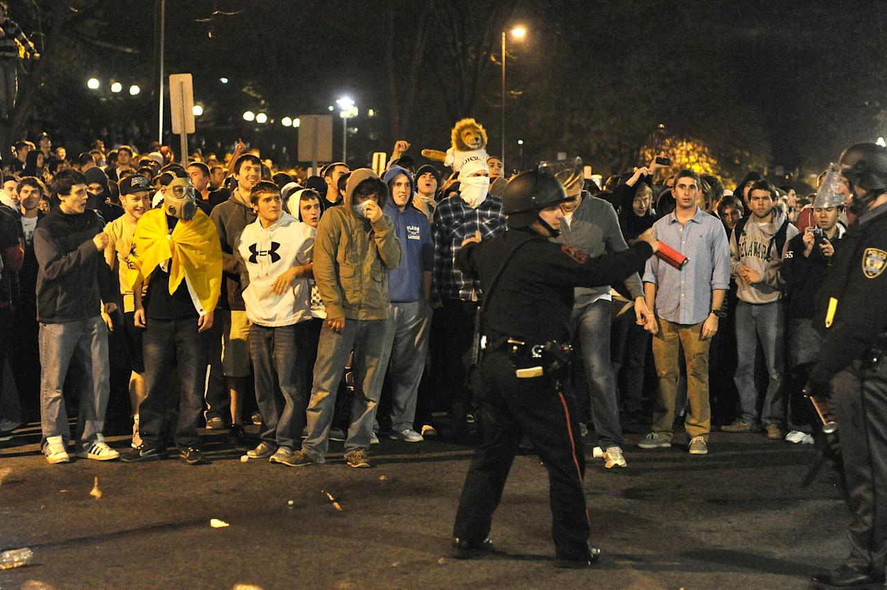 STATE COLLEGE, PA - NOVEMBER 10: Police try to control students and those in the community as they fill the streets and react after football head coach Joe Paterno was fired during the Penn State Board of Trustees Press Conference, in downtown Penn State, in the early morning hours on November 10, 2011 in State College, Pennsylvania. Paterno and Spanier have lost their positions amid allegations that former former Penn State defensive coordinator Jerry Sandusky was involved with child sex abuse. (Photo by Patrick Smith/Getty Images)