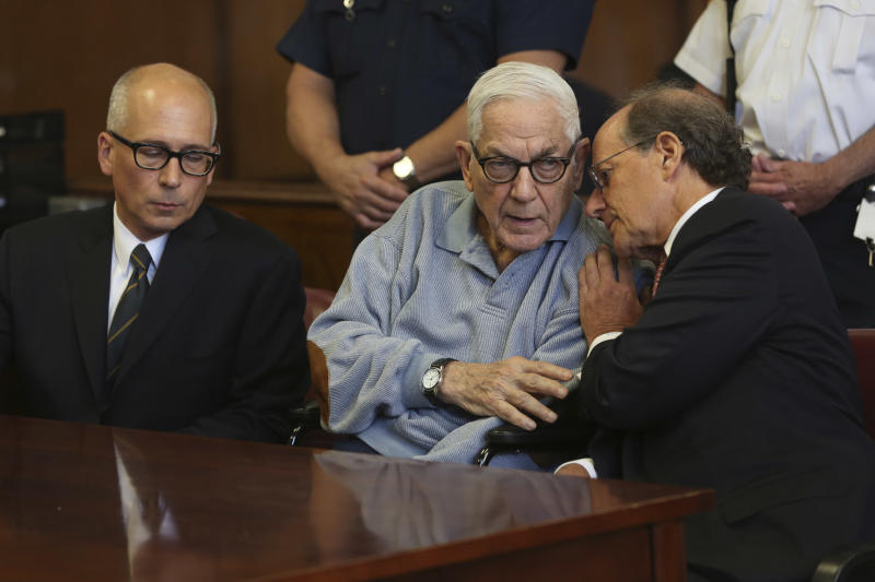 Anthony Marshall, center, speaks to his attorney in criminal court, Friday, June 21, 2013 in New York. The 89-year-old heir convicted of helping himself to his mother Brooke Astor's fortune surrendered Friday to begin his prison term after years of fighting his conviction. (AP Photo/Mary Altaffer)