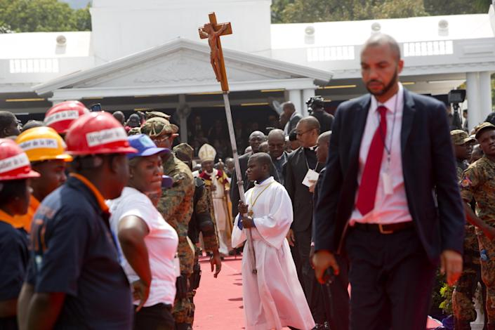 An altar boy carries a cross after a Mass held during the inauguration of of Haiti's new President Jovenel Moise at the National Palace in Port-au-Prince, Haiti, Tuesday Feb. 7, 2017. Moise was sworn as president for the next five years after a bruising two-year election cycle, inheriting a struggling economy and a deeply divided society. (AP Photo/Dieu Nalio Chery)