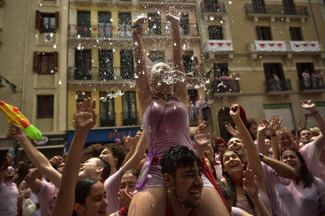<p>Revelers cool down as water is thrown from balconies after the launch of the <em>chupinazo</em> rocket to celebrate the official opening of the 2017 San Fermín Fiesta. (Photo: Alvaro Barrientos/AP) </p>