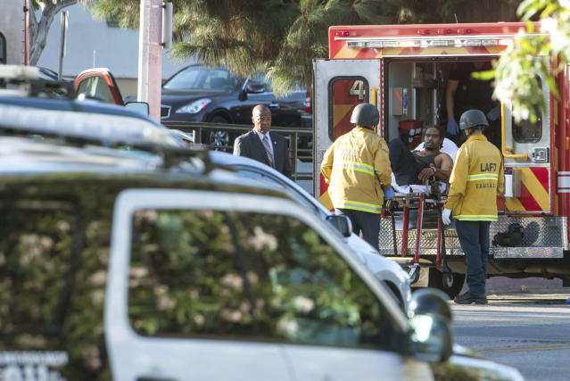 <p>A man is arrested after evading police, holding employees hostage and killing one woman inside of a Treader Joe's in L.A. on Saturday. (Photo: Christian Monterosa via AP) </p>