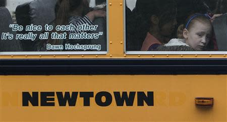 Students sit behind a quote by slain Sandy Hook Elementary School principal Dawn Hochsprung, displayed on the window of a school bus, as it approaches a stop near the original site of Sandy Hook Elementary School in Newtown, Connecticut in this June 14, 2013 file photo. REUTERS/Adrees Latif/Files