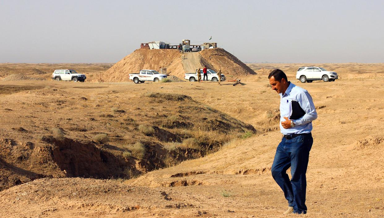 An Iraqi official checks in on progress made by the Swiss Foundation for Mine Action in its efforts to demolish explosives left by ISIS. He walks along the trenches and hills behind the frontline, and a hill fortified by Peshmerga forces to prevent ISIS from getting a view of the demining teams. (Photo: Ash Gallagher for Yahoo News)