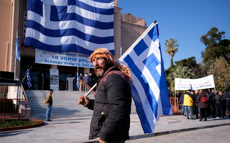 A protester holds a Greek flag outside the Municipality of Mytilene - AP