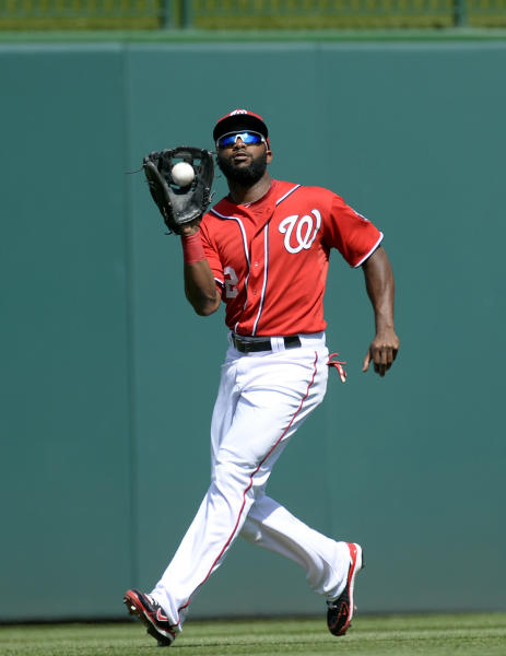 Washington Nationals center fielder Denard Span catches a fly ball hit by Philadelphia Phillies' Jimmy Rollins during the first inning of their baseball game at Nationals Park in Washington, Sunday, Sept. 15, 2013. (AP Photo/Susan Walsh)