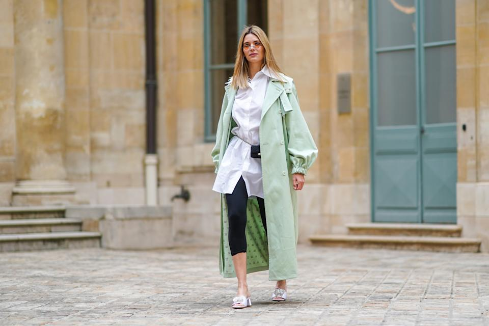 PARIS, FRANCE - MARCH 04: Natalia Verza @mascarada.paris wears sunglasses, a pale pastel mint green long trench coat from Max Mara, a white long shirt, a mini Chanel belt bag, black leggings, white sandals Bling Bling Alzuarr, on March 04, 2021 in Paris, France. (Photo by Edward Berthelot/Getty Images)
