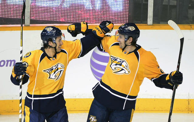 Nashville Predators defenseman Michael Del Zotto, left, celebrates with Simon Moser (5), of Switzerland, after Moser scored a goal in the third period of an NHL hockey game against the Winnipeg Jets on Saturday, March 1, 2014, in Nashville, Tenn. (AP Photo/Mark Zaleski)