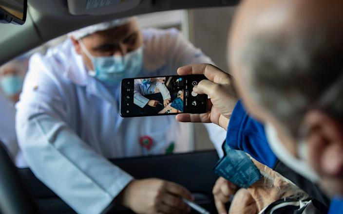 A man photographs his mother getting a shot of China's Sinovac CoronaVac vaccine at a drive-thru site set up in the Pacaembu soccer stadium car park in Sao Paulo, Brazil - Andre Penner/AP