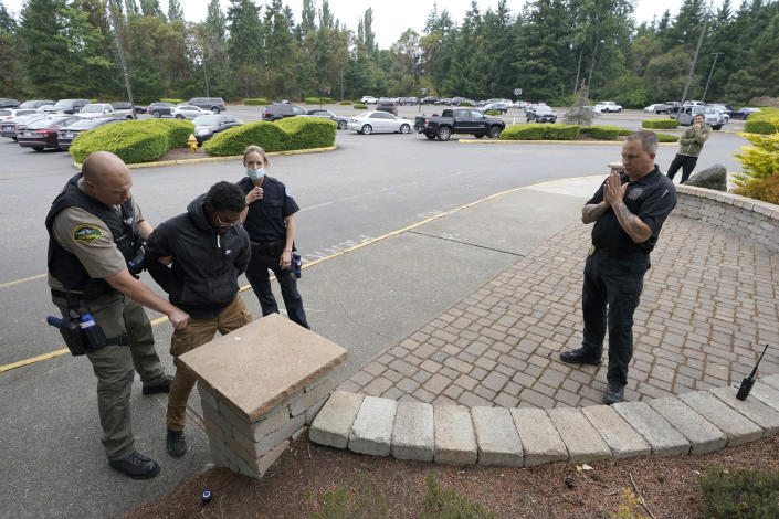 Ken Westphal, right, an officer with the Lacey Police Dept. and an instructor at the Washington state Criminal Justice Training Commission, works with cadets Kevin Burton-Crow, left, of the Thurston Co. Sheriff's Dept., and LeAnne Cone, third from left, of the Vancouver Police Dept., as they search an actor playing a person who has caused a disturbance at a convenience store during a training exercise Wednesday, July 14, 2021, in Burien, Wash. Washington state is embarking on a massive experiment in police reform and accountability following the racial justice protests that erupted after George Floyd's murder last year, with nearly a dozen new laws that took effect Sunday, July 25 but law enforcement officials remain uncertain about what they require in how officers might respond — or not respond — to certain situations, including active crime scenes and mental health crises. (AP Photo/Ted S. Warren)