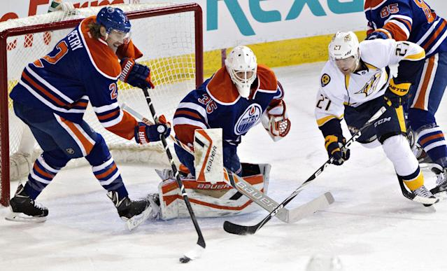 Nashville Predators' Patric Hornqvist (27) and Edmonton Oilers' Jeff Petry (2) vie for a rebound after goalie Viktor Fasth (35) made a save during the first period of an NHL hockey game Tuesday, March 18, 2014, in Edmonton, Alberta. (AP Photo/The Canadian Press, Jason Franson)