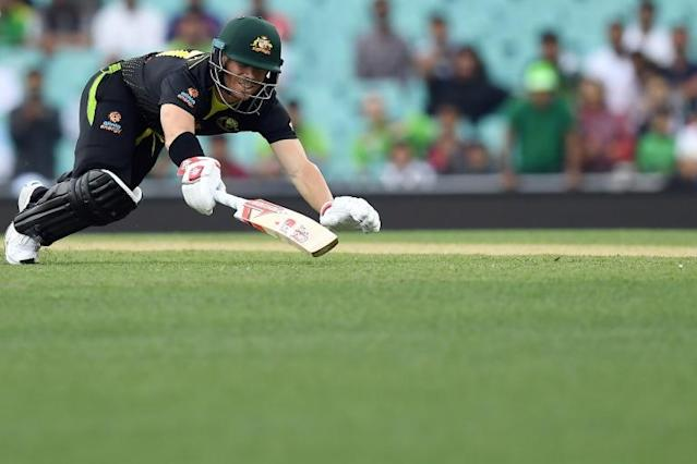 Australia's David Warner dives in an attempt to avoid a run out during the Twenty20 match between Australia and Pakistan at the Cricket Cricket Ground in Sydney, The match ended in no result after rain (AFP Photo/Saeed KHAN)