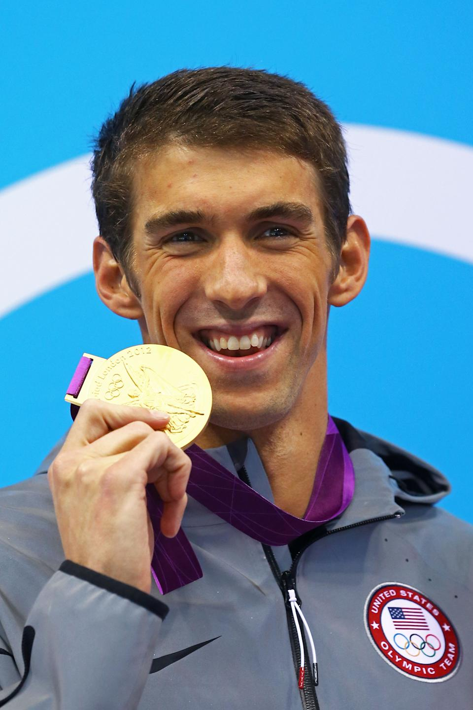 <b>Medal No. 21</b><br>Gold medalist Michael Phelps of the United States poses on the podium during the medal ceremony for the Men's 100m Butterfly Final on Day 7 of the London 2012 Olympic Games at the Aquatics Centre on August 3, 2012 in London, England. (Photo by Al Bello/Getty Images)