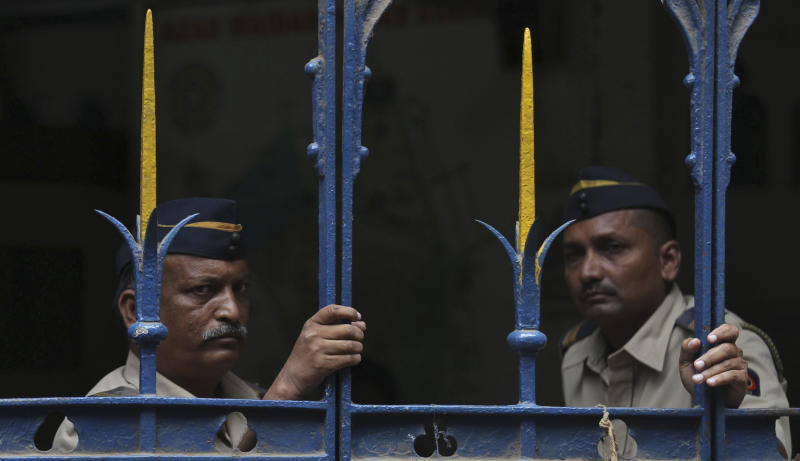 Indian policemen stand guard at a court during a hearing of one of the accused in the gang rape of a photojournalist in Mumbai, India, Sunday, Aug. 25, 2013. Police on Sunday arrested the last of five men wanted in the gang rape of a 22-year-old Indian woman in Mumbai, and said charges would be filed soon in a case that has incensed the public and fueled debate over whether women can be safe in India.(AP Photo/Rafiq Maqbool)