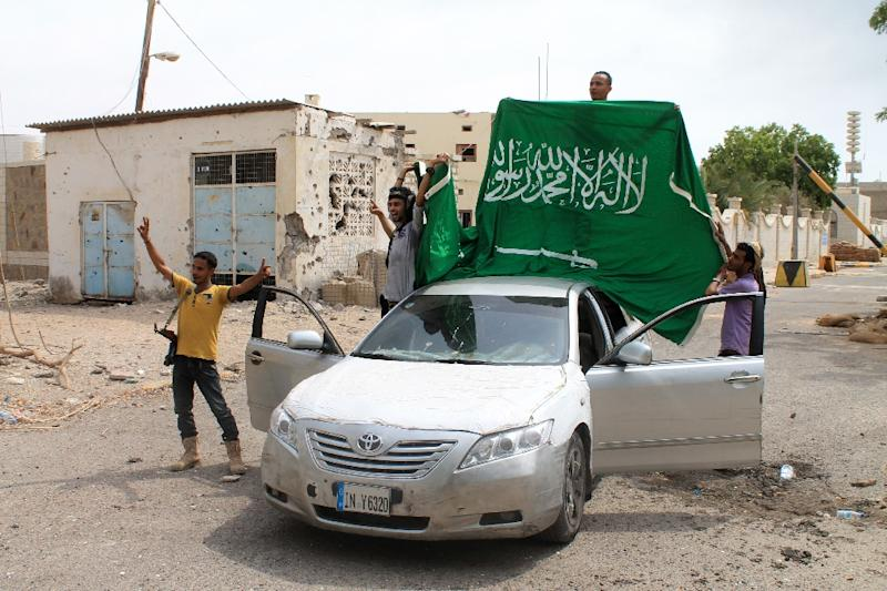 Yemeni fighters loyal to exiled President Abedrabbo Mansour Hadi deploy a Saudi national flag next to the Saudi consulate after they retook it from Shiite Huthi rebels in the southern Yemeni city of Aden on July 16, 2015 (AFP Photo/Saleh al-Obeidi)