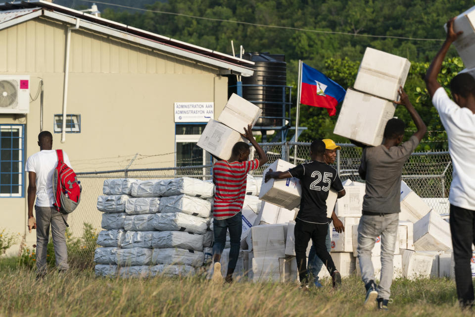 """Haitian aid workers move aid boxes after unloading a VM-22 Osprey at Jeremie Airport, Saturday, Aug. 28, 2021, in Jeremie, Haiti. The VMM-266, """"Fighting Griffins,"""" from Marine Corps Air Station New River, from Jacksonville, N.C., are flying in support of Joint Task Force Haiti after a 7.2 magnitude earthquake on Aug. 22, caused heavy damage to the country. (AP Photo/Alex Brandon)"""