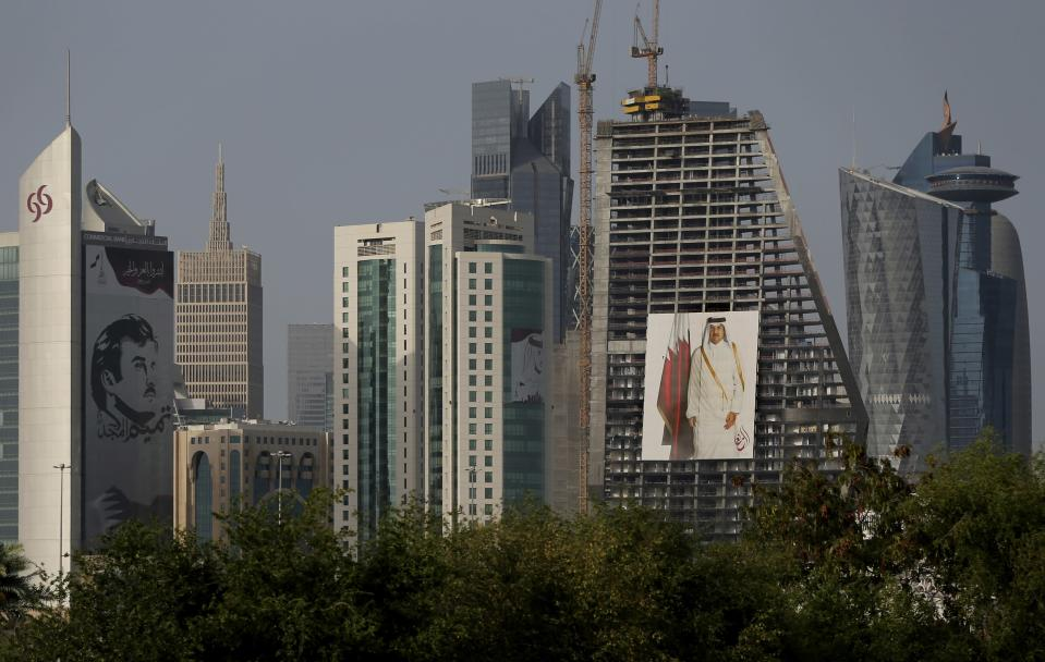FILE - In this May 5, 2018, file photo, the images of the Emir of Qatar, Sheikh Tamim bin Hamad Al Thani hang on the towers in Doha, Qatar. Qataris awoke to a surprise blockade and boycott by Gulf Arab neighbors 3 1/2 years ago, and this week were jolted again by the sudden announcement that it was all over. (AP Photo/Kamran Jebreili, File)