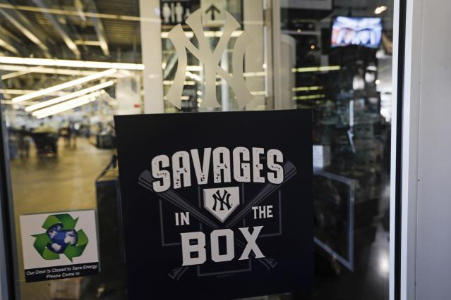 """Employees pass signage for the """"Savages in the Box"""" at the New York Yankees team Store before the second game of a baseball doubleheader against the Baltimore Orioles, Monday, Aug. 12, 2019, in New York. (AP Photo/Frank Franklin II)"""