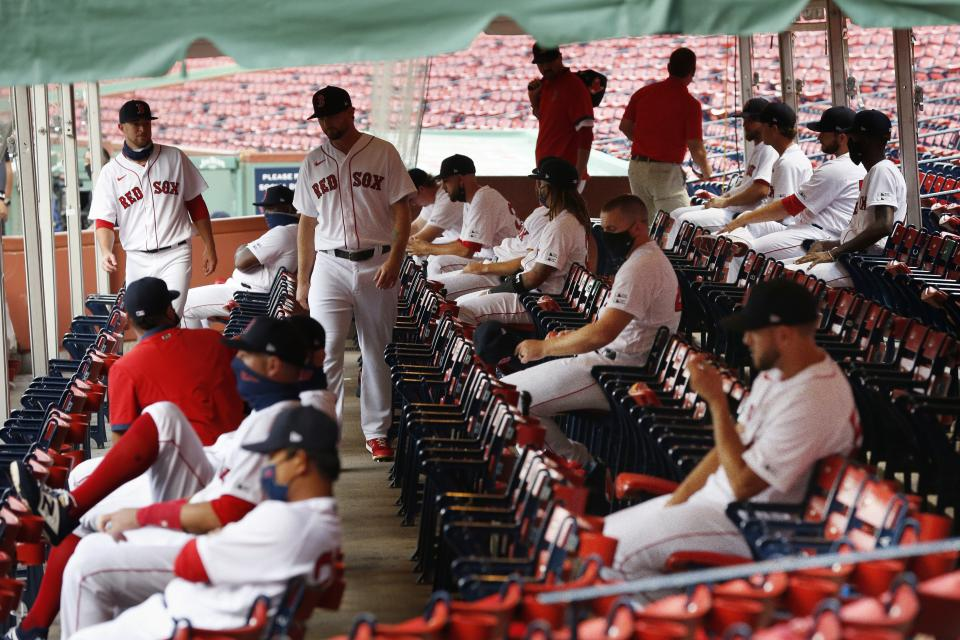 Boston Red Sox players practice social distancing in an expanded dugout during the first inning of an opening day baseball game against the Baltimore Orioles at Fenway Park, Friday, July 24, 2020, in Boston. (AP Photo/Michael Dwyer)
