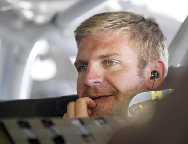 Clint Bowyer scratches his face as he looks out from his car during practice for Sunday's NASCAR Sprint Cup Series auto race at New Hampshire Motor Speedway, Friday, Sept. 20, 2013, in Loudon, N.H. (AP Photo/Mary Schwalm)