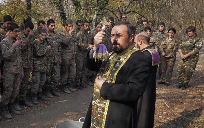 Priests Aristakes Hovhannisyan, right, and Sebeos Galachyan conduct a baptism ceremony for ethnic Armenian soldiers in a military camp near the front line during a military conflict in separatist region of Nagorno-Karabakh, Monday, Nov. 2, 2020. Fighting over the separatist territory of Nagorno-Karabakh entered sixth week on Sunday, with Armenian and Azerbaijani forces blaming each other for new attacks. (AP Photo)