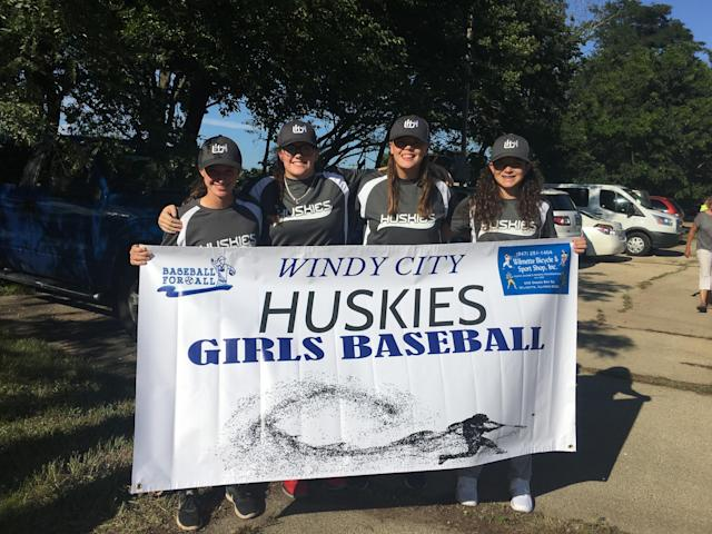 Four members of the Windy City Huskies roll out their banner before the parade. (Liz Roscher)