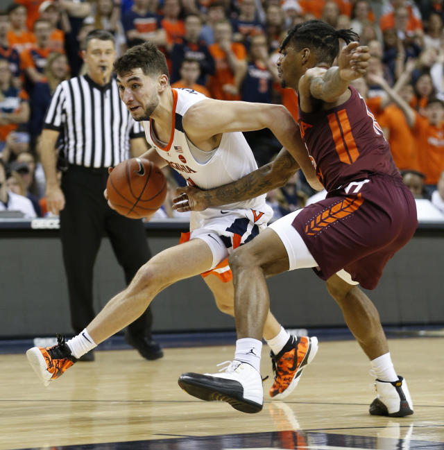 Virginia guard Ty Jerome (11) drives past Virginia Tech guard Ahmed Hill, right, during the first half of an NCAA college basketball game in Charlottesville, Va., Tuesday, Jan. 15, 2019. (AP Photo/Steve Helber)
