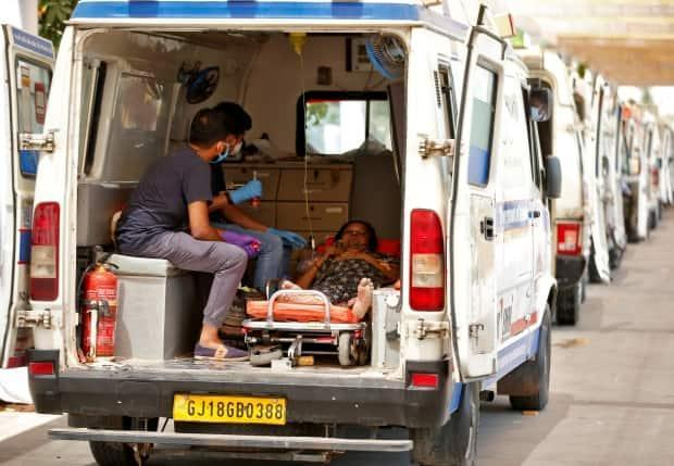 A woman with breathing problem waits inside an ambulance for her turn to enter a COVID-19 hospital for treatment, amidst the spread of the coronavirus disease in Ahmedabad, India.