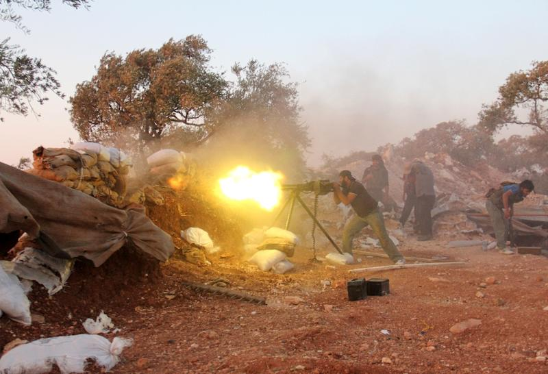 A rebel fighter fires a heavy machine gun during clashes with government forces and pro-regime shabiha militiamen on the outskirts of Syria's northwestern Idlib province on September 18, 2015 (AFP Photo/Omar Haj Kadour)